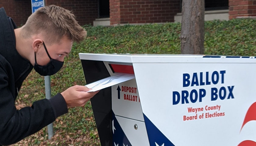 Man putting in mail-in vote in drop box with mask on