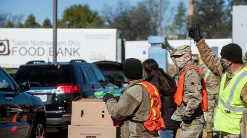 Soldiers assigned the Ohio National Guard's HHC 1-148th Infantry Regiment – 37th Infantry Brigade Combat Team and the Ohio Military Reserve, give the thumbs-up for troopers assigned to the Ohio State Highway Patrol, to send more vehicles through the line at a drive through food distribution event at the Toledo Northwestern Ohio Food Bank, May 9, 2020. The food bank teamed up with the Ohio National Guard and the Highway Patrol to conduct the first-ever drive through event at the food bank. More than 700 Ohio National Guard and Ohio Military Reserve members were activated to provide humanitarian missions in support of Operation Steady Resolve COVID-19 relief efforts, continuing The Ohio National Guard's long history of supporting humanitarian efforts throughout Ohio and the nation. To date, the Ohio National Guard has assisted in the distribution of more than 9.9 million pounds of food and pantry items to Ohioans in need. (Air National Guard photo by Senior Master Sgt. Beth Holliker)
