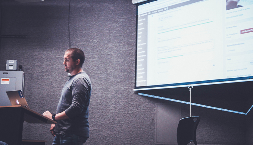 Man standing in front of a room, giving a lecture with a presentation